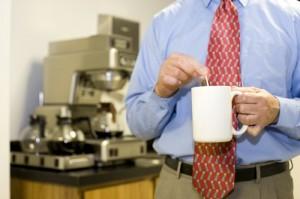 Büromitarbeiter rührt Kaffee um