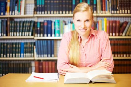 Studentin liest in einem Buch und macht sich Notizen
