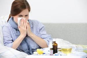 Frau mit Grippe und Medikamenten