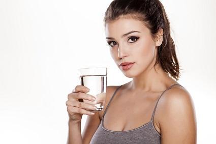 Junge Frau trinkt Glas Wasser